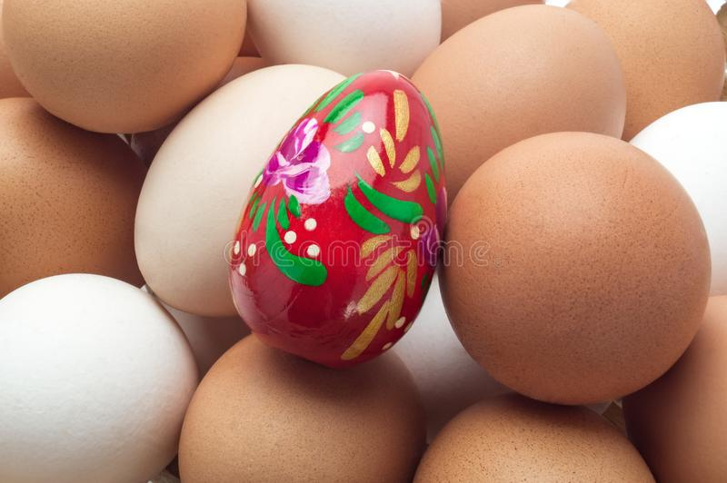 Egg Easter red on the background of unpainted eggs. stock image