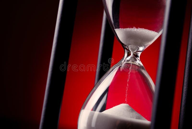 Egg el contador de tiempo o el reloj de arena en un fondo rojo imagenes de archivo