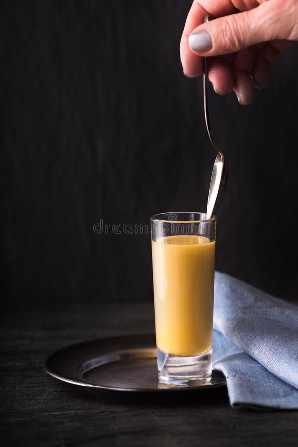 Egg el licor en el vidrio con la cuchara en la vertical de la mano fotos de archivo libres de regalías