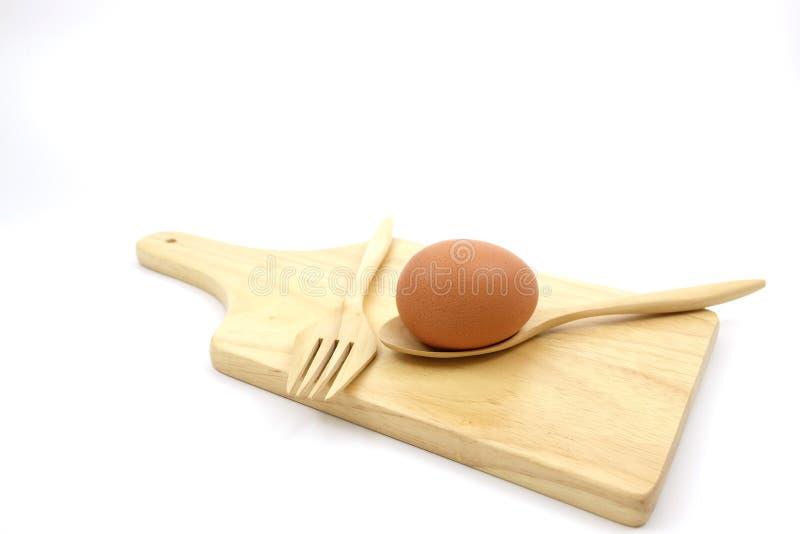 Egg en la placa de madera con las cucharas de madera y la bifurcación de madera fotografía de archivo libre de regalías