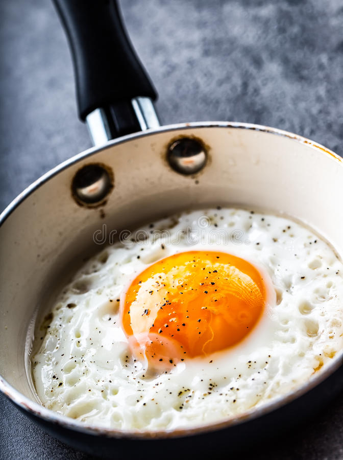 Egg. Fried egg. Chicken egg. Close up view of the fried egg on a frying pan. Salted and spiced fried egg royalty free stock images