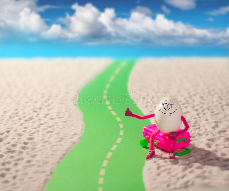 Egg girl hitchhiking in a sand desert. Funny egg girl hitchhiking on a road in a sand desert. Travel concept royalty free stock photo