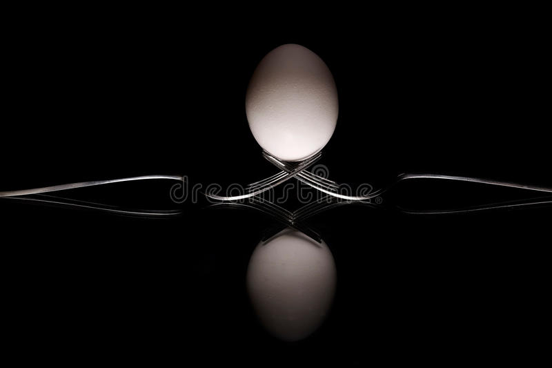 Egg Holder. An egg balancing on two forks with a reflective surface stock image