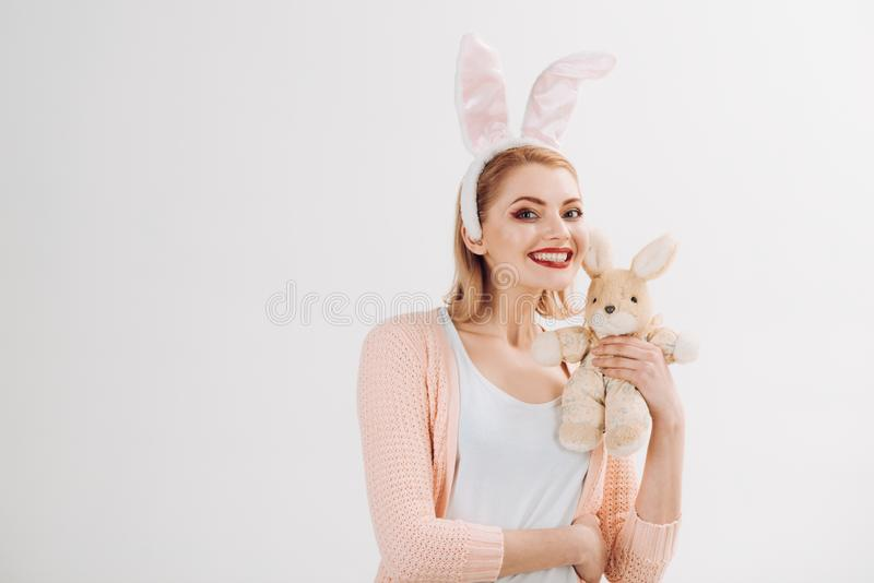 Egg hunt. Easter eggs as traditional food. Spring holiday. Girl with hare toy. Woman in rabbit bunny ears. happy woman. In bunny ears with toy. Happy easter royalty free stock photos