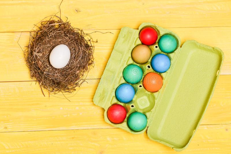 Egg hunt. painted eggs in egg tray. Spring holiday. Holiday celebration, preparation. New life in straw nest. Healthy royalty free stock photography