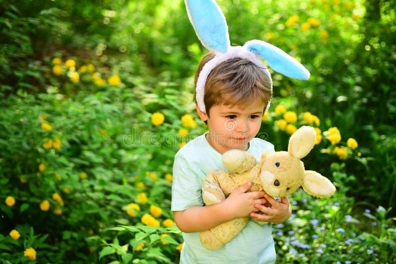 Egg hunt on spring holiday. Little boy child in green forest. love easter. Family holiday. Happy easter. Childhood. Rabbit kid with bunny ears. Hare toy royalty free stock photo