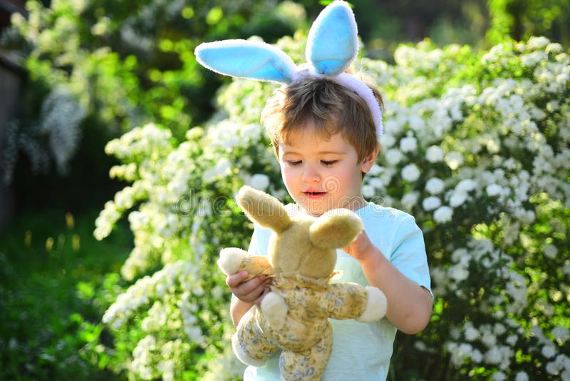 Egg hunt on spring holiday. Rabbit kid with bunny ears. Hare toy. Little boy child in green forest. love easter. Family stock photos