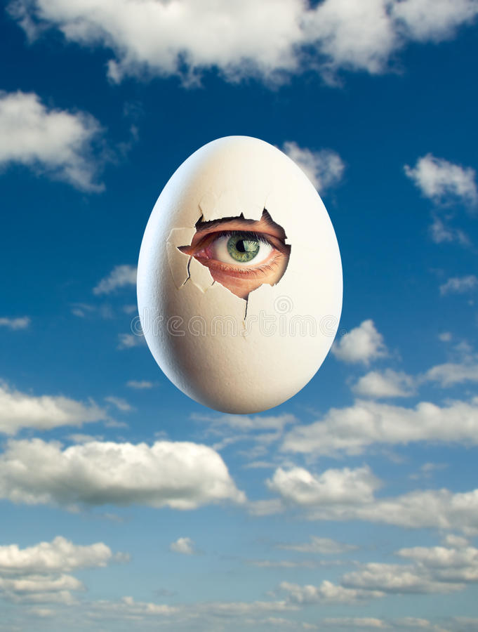 Egg isolated on blue background with eye inside. Close-up broken white egg with eye inside royalty free stock photography