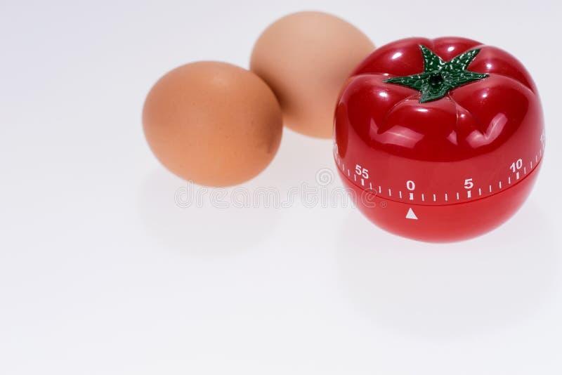 Egg la maquette de minuterie sous forme de tomate avec deux oeufs photographie stock libre de droits