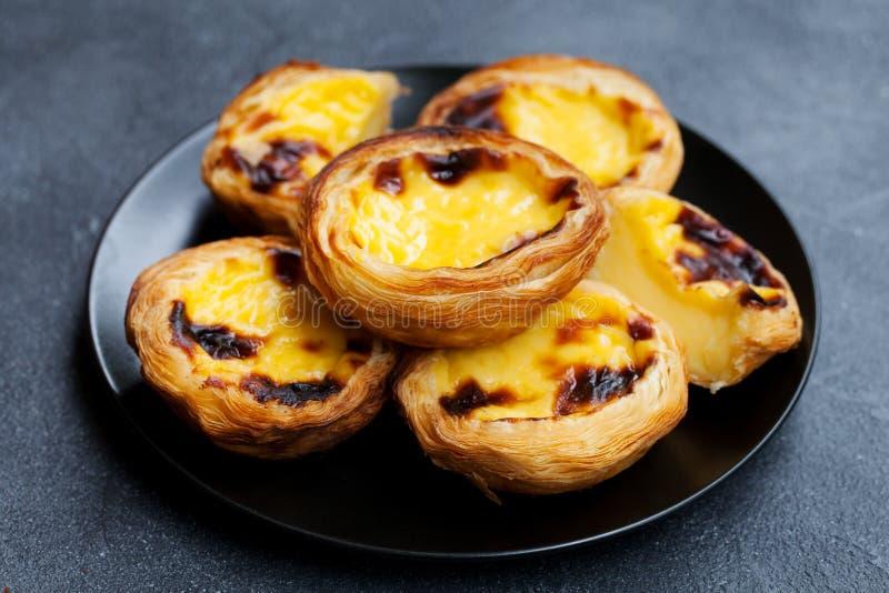 Egg la tarte, le dessert portugais traditionnel, le Pastel de nata d'un plat Fond en pierre gris photos libres de droits