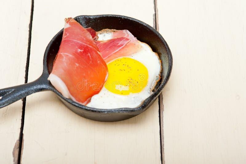 Egg le côté ensoleillé avec du jambon italien de point photographie stock