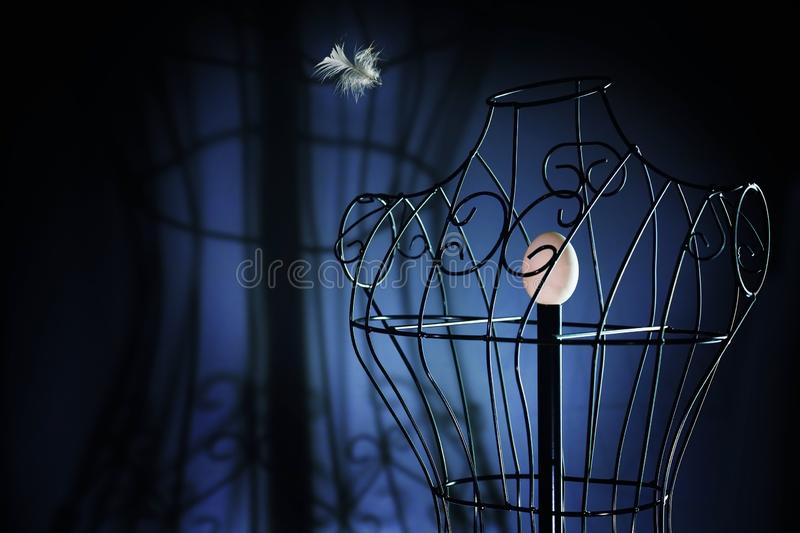 Egg in a metal tailor doll like in a bird cage and a flying feather, surreal art concept for longing and loneliness, dark blue. Background with copy space stock photo