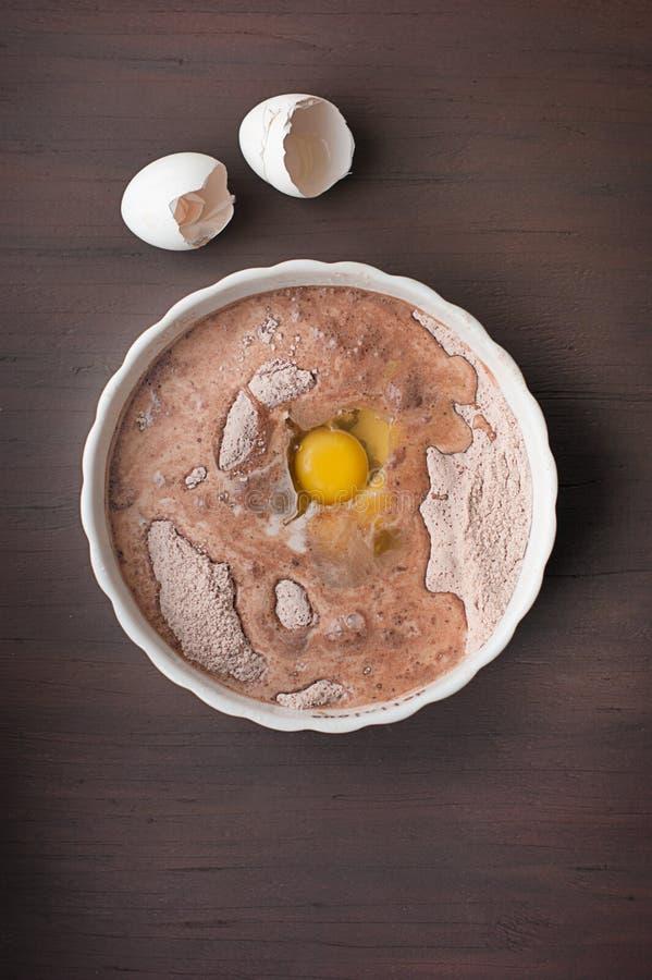 Egg a mistura para cozer e os shell em um fundo de madeira escuro foto de stock royalty free