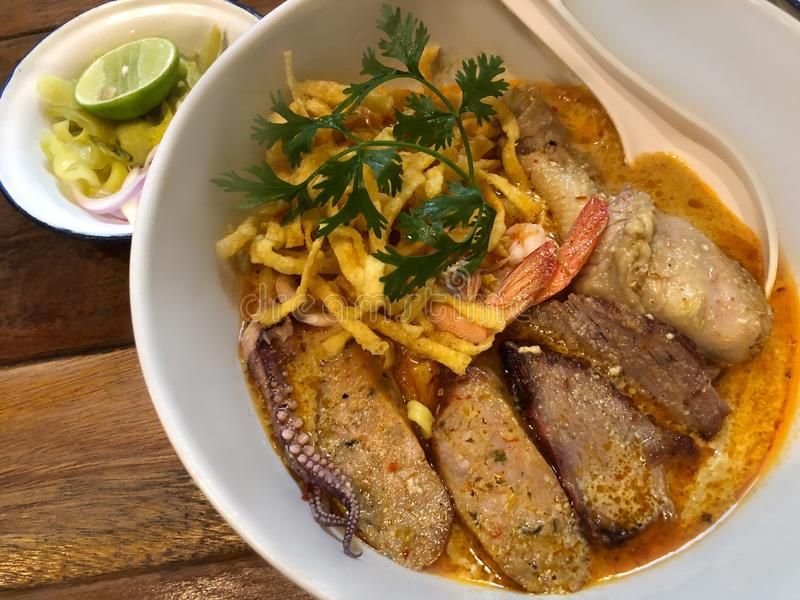 Egg noodle in curry, serving with variety of ingredients such as pork, squid, shrimp. Traditional food of Northern Thailand, Khao. Soi Recipe stock images