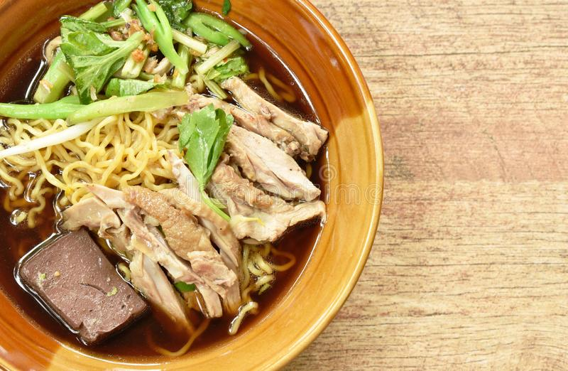 Egg noodles with boiled duck in Chinese herb brown soup on bowl. Egg noodles with boiled duck in Chinese herb brown soup on the bowl stock image