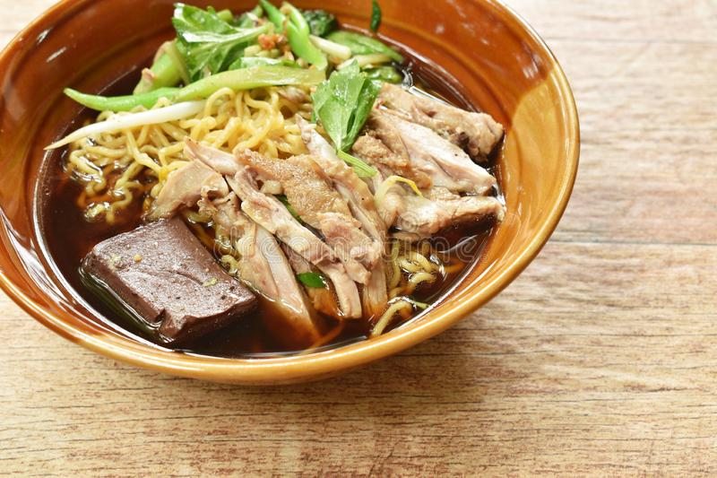 Egg noodles with boiled duck in Chinese herb brown soup on bowl. Egg noodles with boiled duck in Chinese herb brown soup on the bowl stock photos