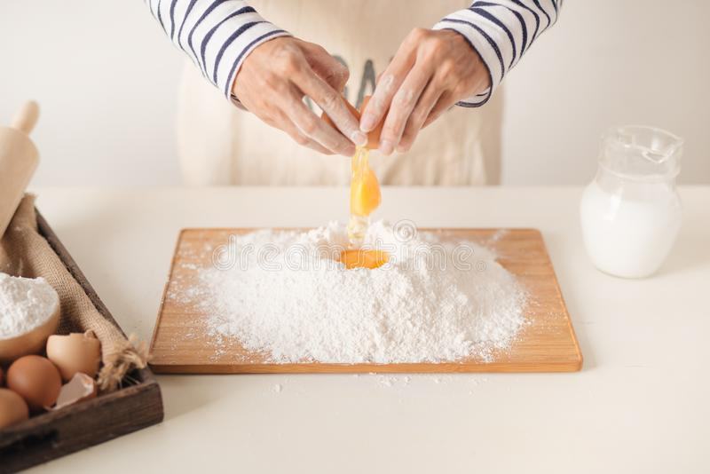 Egg poured into flour during the baking process, man`s hands.  royalty free stock photography