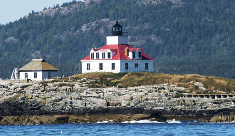 Egg Rock Lighthouse in Bar Harbor, Maine. Egg Rock lighthouse on a sunny afternoon with Acadia National Parks Cadillac Mountain behind it, in Bar Harbor Maine stock image