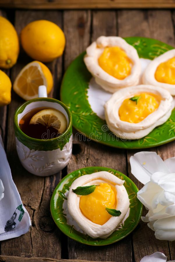 Egg shaped meringue nests with lemon curd.traditional easter pastries stock photography