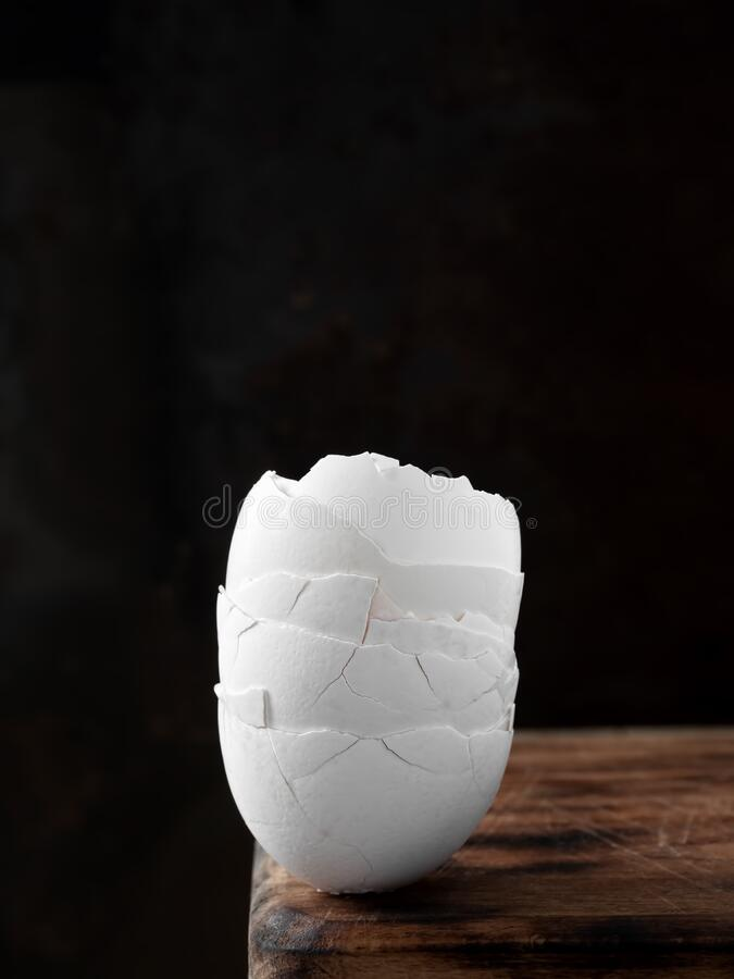Egg shell broken crack on wooden background. Close Up, Vertical orientation. Copy space.  stock photos