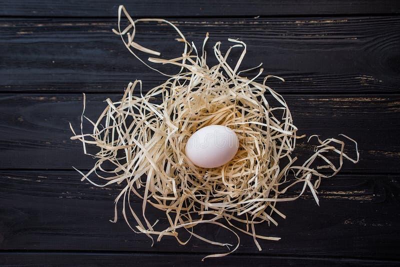 Egg in straw nest on black wooden desc. Egg in straw nest on black wooden desk. Top view royalty free stock photo