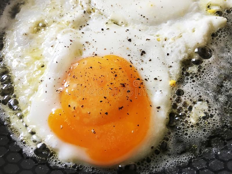 Egg sunny-side up in a hot pan stock image