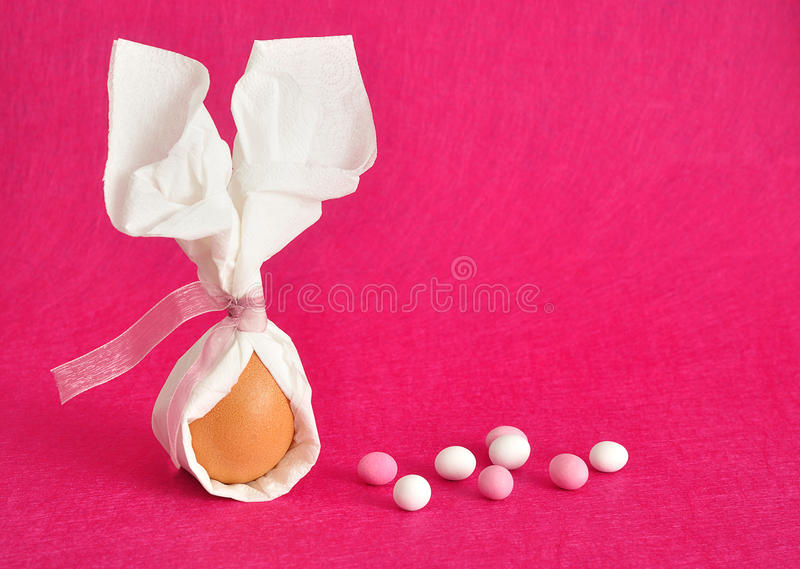 An egg tied in a serviette that looks like bunny ears. For easter displayed with candy on a pink background royalty free stock images