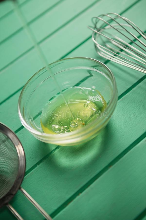 Egg white falling in bowl by wire whisk royalty free stock images