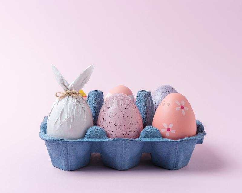 Egg wrapped in a paper in the shape of a bunny with colorful Easter eggs in carton tray. Minimal Easter concept stock images