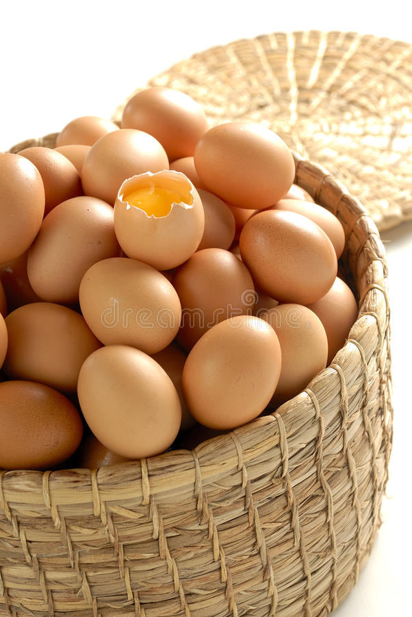 Egg yolk. On pile of eggs, in a basket stock photo