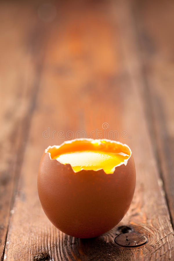 Egg with Yolk. Opened Egg Shell with Yolk on Wood royalty free stock photo