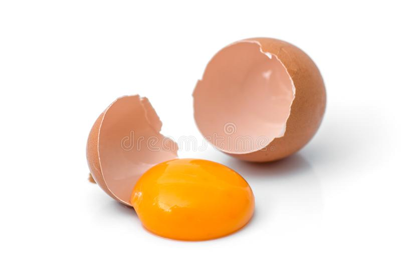 Egg yolk in egg shell. Cracked egg white isolated on white background stock image