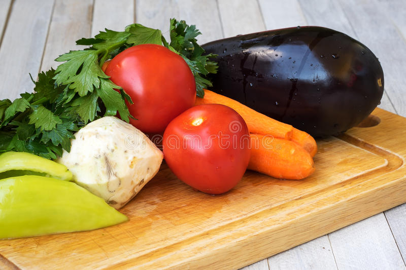 Eggplant, celery, carrots, tomatoes and peppers prepared for cooking stock photos