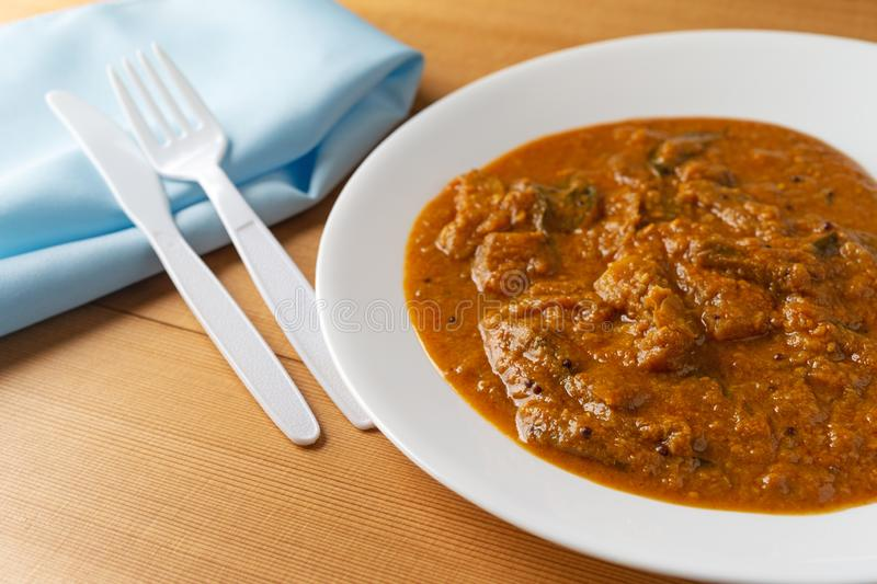 Eggplant curry meal on a white plate with plastic fork and knife royalty free stock image