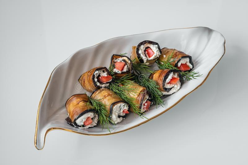 Eggplant rolls with cottage cheese and tomato with dill branches on a decorative white plate in the shape of a leaf close-up on a royalty free stock photos