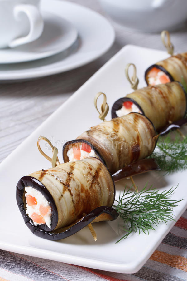 Eggplant rolls with cream cheese and tomatoes vertical stock image