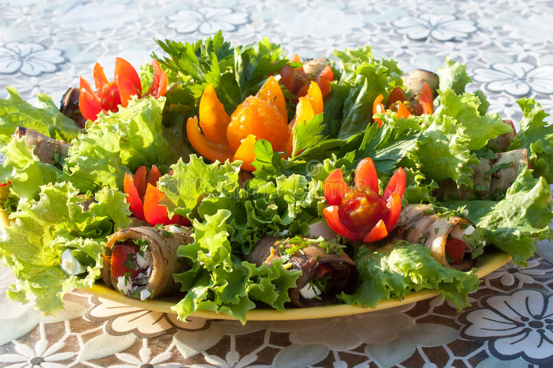 Rolls from eggplant and lettuce leaves decorated with flowers cut from cherry tomatoes on a white tablecloth side view royalty free stock photo