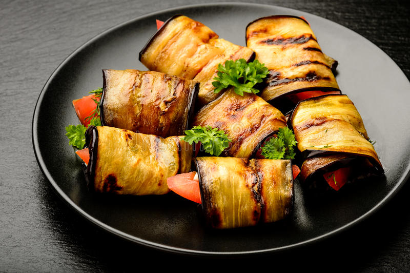 Eggplant rolls with tomatoes, garlic and dill. stock photography
