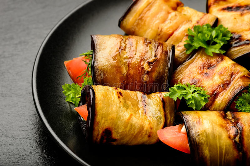 Eggplant rolls with tomatoes, garlic and dill. royalty free stock image