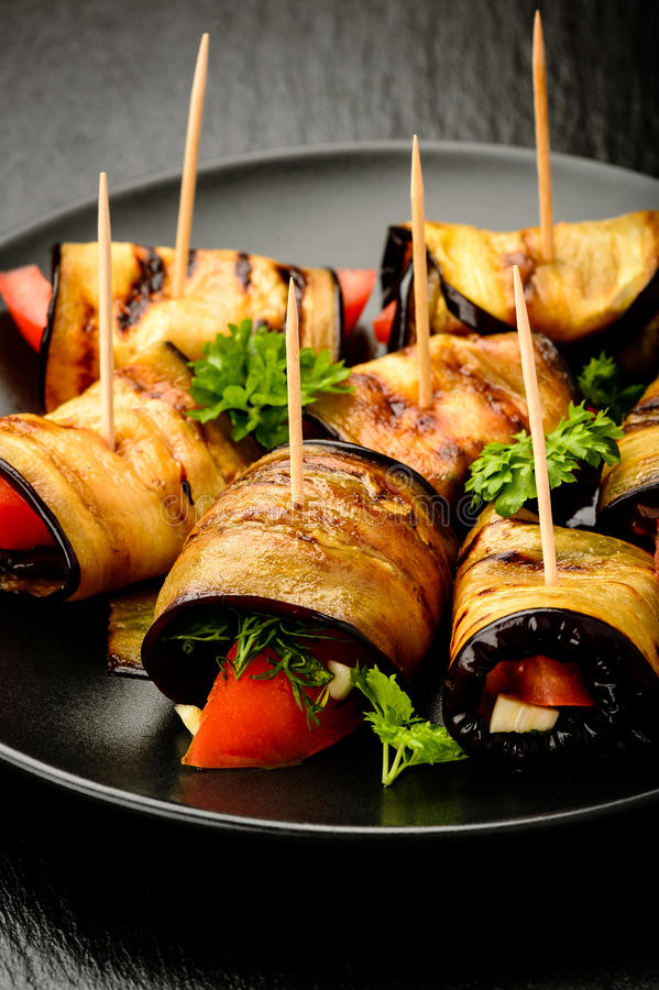 Eggplant rolls with tomatoes, garlic and dill. royalty free stock photography