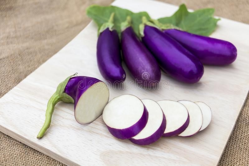 Eggplant violet raw on wooden cutting board and on sackcloth background, it is vegetable food for healthy stock images