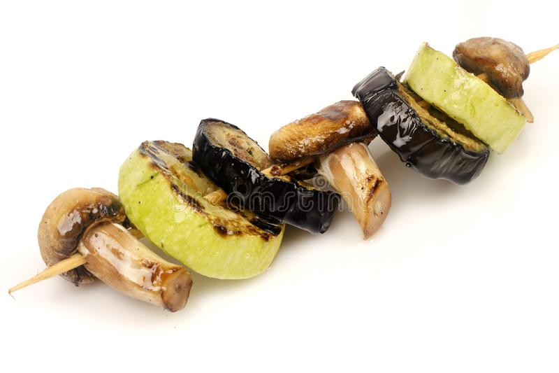 Eggplant, zucchini and mushrooms champignons grilled on a grill on a spit. On a white background for isolation royalty free stock photography