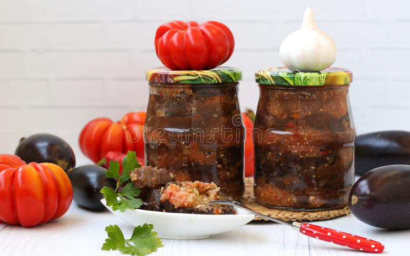 Eggplants in acute sauce of pepper, tomatoes and garlic in jars on the table. royalty free stock photo