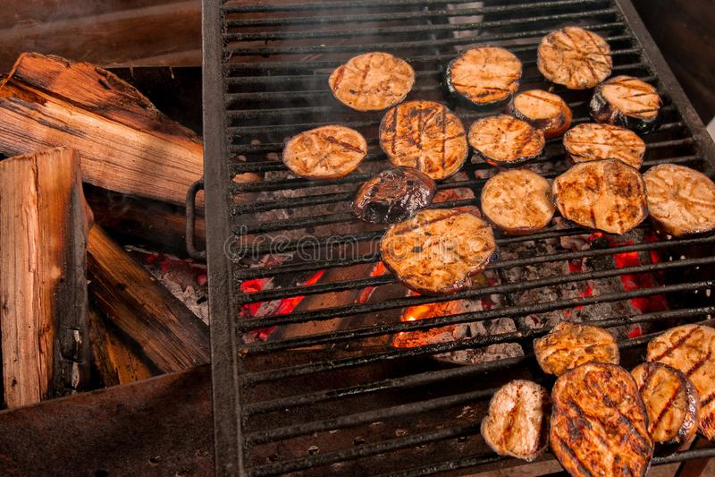 Eggplants grill. Vegetables are fried or baked on open fire. Barbecue kitchen party close up image. Cooking on wire rack royalty free stock image