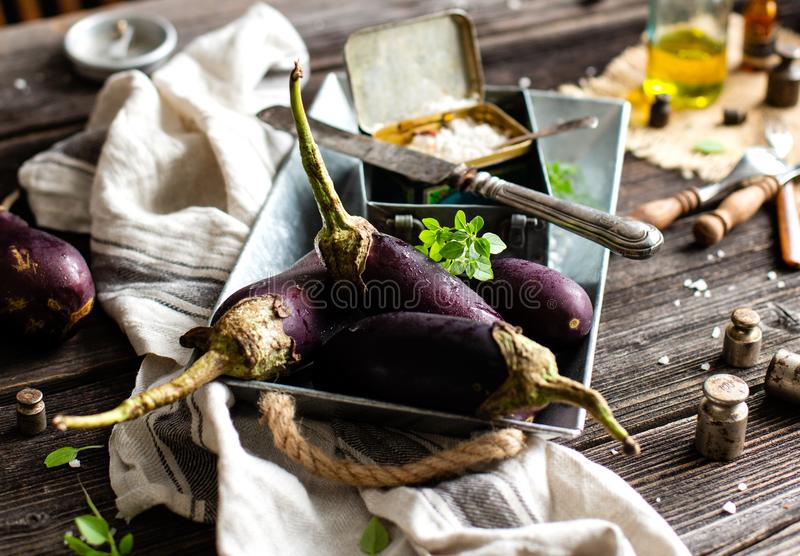 Eggplants on metal vintage tray with basil, salt, knife on rustic wooden table stock photos
