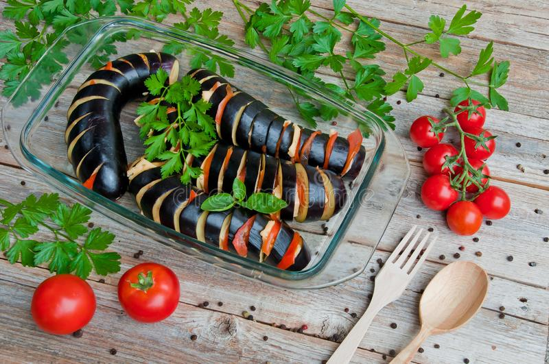 Eggplants sliced for baking with cheese and tomatoes in a transparent bowl stock photography