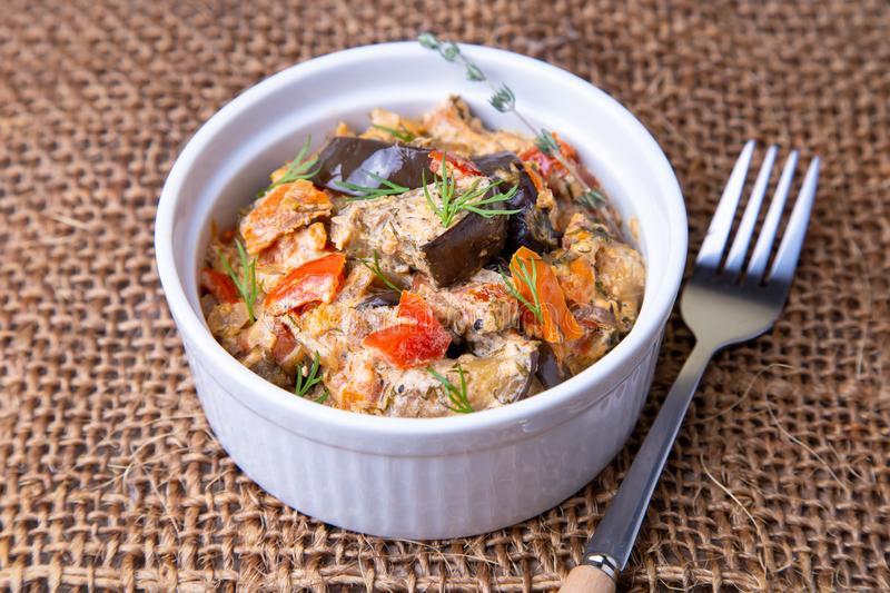 Eggplants with tomatoes, bulgarian red sweet pepper, onion, dill and sour cream. stock photo