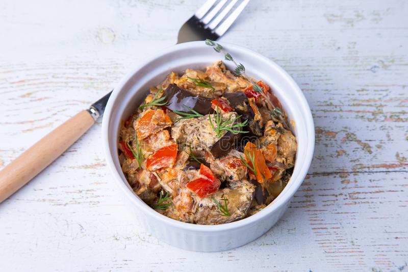 Eggplants with tomatoes, bulgarian red sweet pepper, onion, dill and sour cream. royalty free stock photography