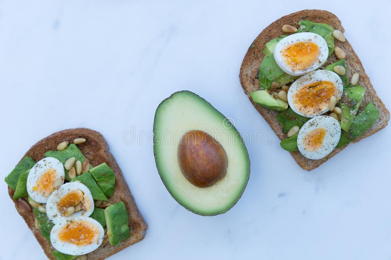 Eggs and avocado on toast on white marble background flat lay royalty free stock photo