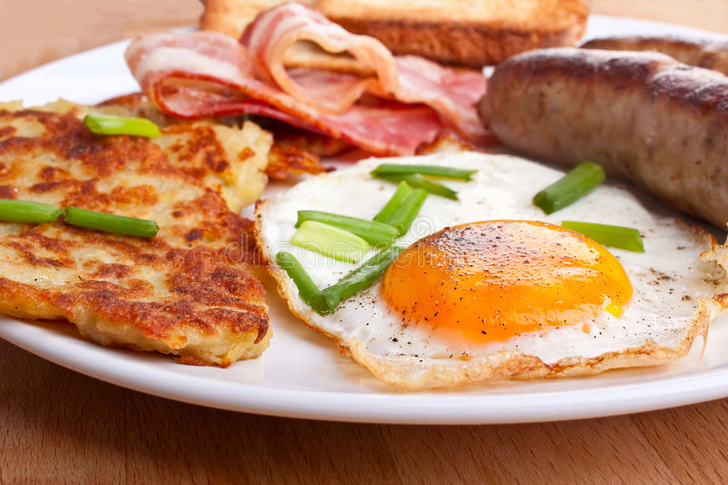 Eggs and bacon breakfast. Classic eggs, hash browns and bacon breakfast royalty free stock photos